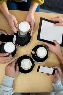 Friends using mobile phone and digital tablet while having cup of coffee in cafx92xA9