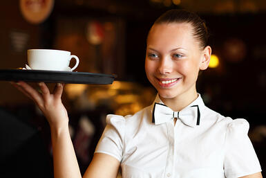 Portrait of young waitress in white blouse holding a tray
